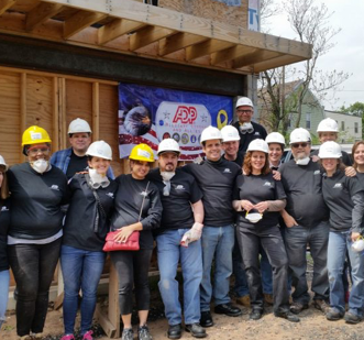 group of ADP associates wearing black ADP T-shirts and construction hardhats