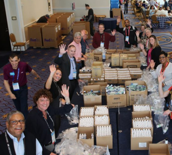 group of ADP associates waving hello while packing boxes