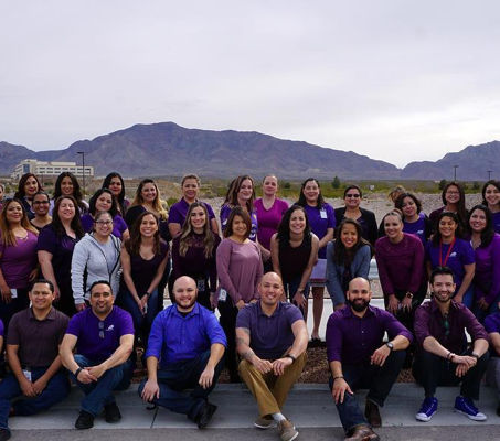 team of ADP El Paso associates standing and seated outdoors with mountain in the background