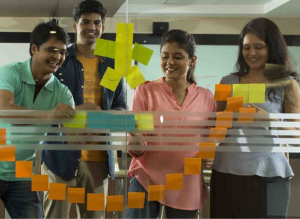 group of ADP associates creating a smiley face on a glass wall out of Post-It Notes