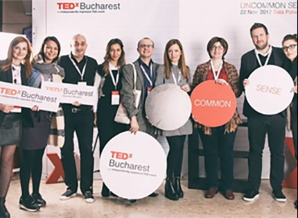 group of ADP associates holding TED Bucharest signage