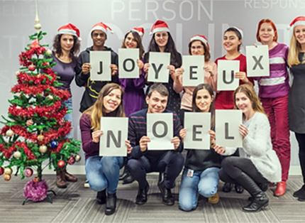 group of ADP associates in Santa hats holding letters that spell JOYEUX NOEL