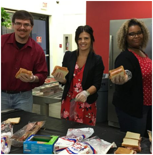 three ADP associates holding sandwiches