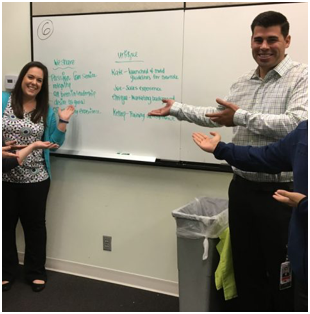 two ADP associates pointing at a whiteboard