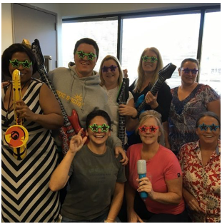 group of ADP associates wearing colorful, star-shaped sunglasses