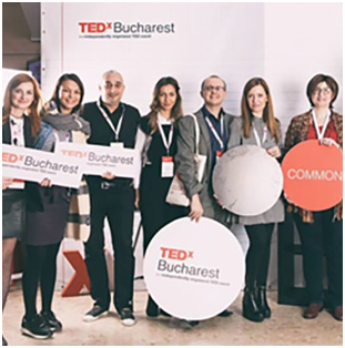 group of ADP associates holding TEDx Bucharest signage