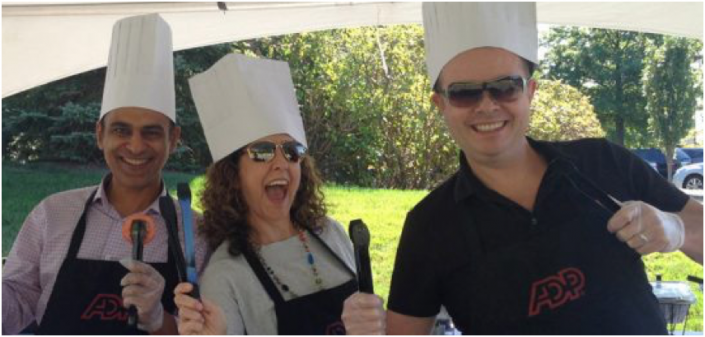 three ADP associates wearing chef's hats and holding BBQ utensils