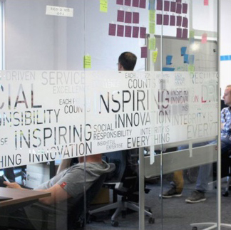 glass wall with some words etched into it: inspiring, innovation, social responsibility, integrity is everything