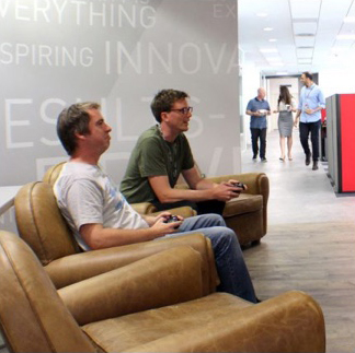 two ADP associates seated on lounge chairs with game controllers in their hands