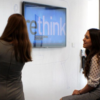 "two women looking at a large white board/wall; the word ""rethink"" is displayed on a monitor on the wall beside them"