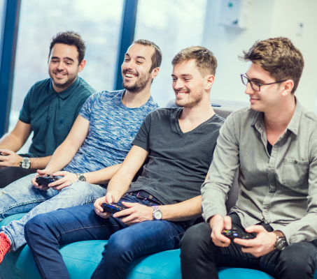four young guys with game consoles in their hands