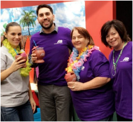 ADP associates in purple T-shirts with some wearing Hawaiian leis and holding tropical drinks