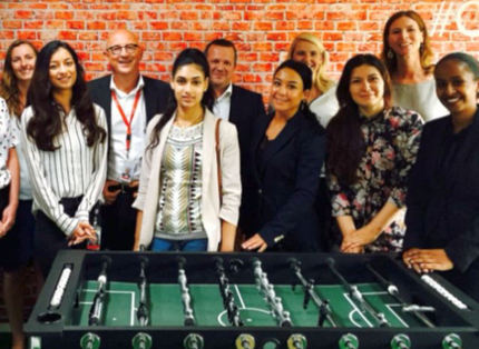 group of ADP associates standing behind a foosball table