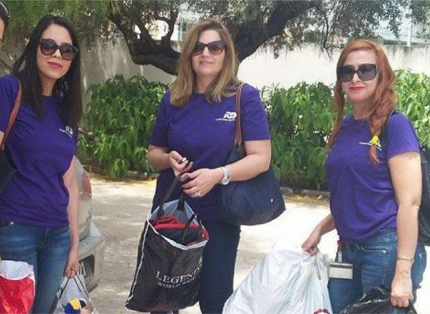 three women ADP associates wearing purple T-shirts and sunglasses