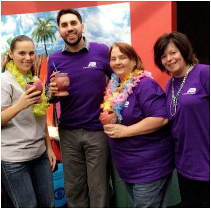 group of ADP associates in purple T-shirts holding tropical drinks