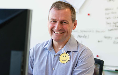 smiling ADP associate with a smiley face tied to his shirt collar