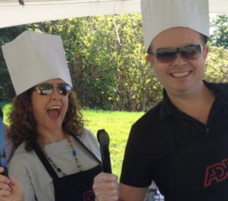 two ADP associates in chef hats and holding BBQ utensils