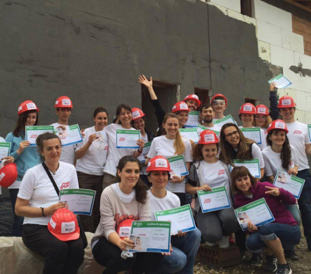 group of ADP associates wearing white T-shirts and red construction hardhats