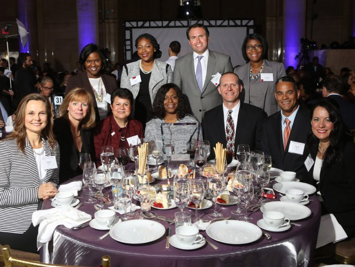 ADP associates seated and standing around an awards banquet table.