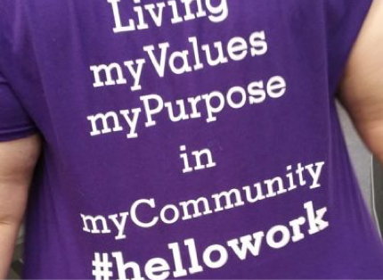 "woman wearing purple T-shirt with the words ""Living my Values, my Purpose in my Community. #hellowork"