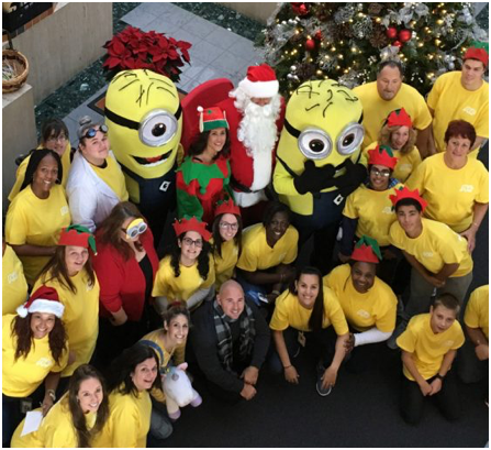 large group of ADP associates wearing yellow T-shirts surround Santa Claus, an elf, and two minion characters from the movie, Despicable Me.