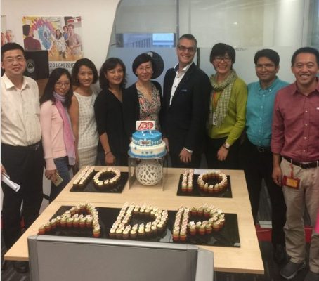 ADP China associates standing around a 10-year anniversary cake""