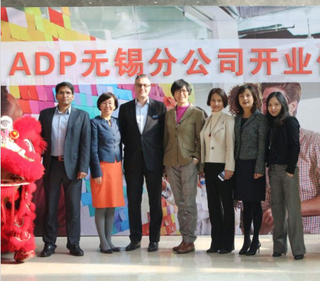 group of ADP China associates standing between red and yellow Chinese lions