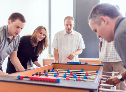 ADP associates playing Foosball.