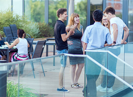 A group of ADP associates having a discussion on a terrace.