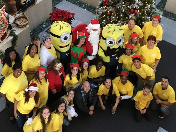large group of ADP associates wearing yellow T-shirts, standing around Santa Claus, an elf, and two minion characters from the movie 'Despicable Me.'