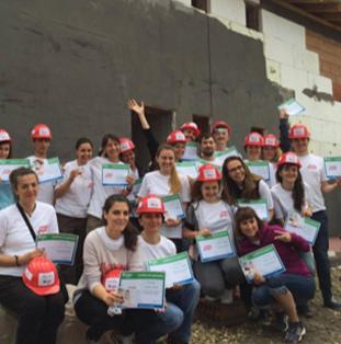 skupina zaměstnanců ADP, kteří mají na sobě bílá trička a červené helmy
