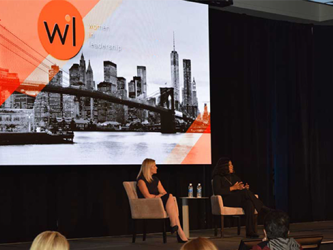 two women seated on a stage at the Women in Leadership conference