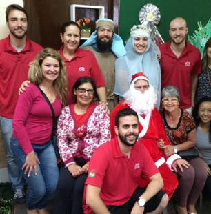 zaměstnanci ADP v červených tričkách, kteří pózují kolem Santa Clause a biblických postav Marie a Josefa