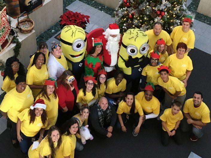 velká skupina zaměstnanců ADP ve žlutých tričkách stojící kolem Santa Clause, elfa a dvou postaviček Mimoňů z filmu Já, padouch.