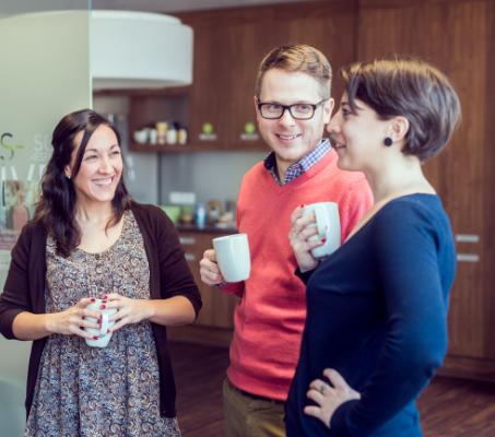 Čtyři zaměstnanci ADP drží hrnky s kávou