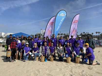 large team of volunteer ADP associates standing and kneeling in two rows on a sandy beach