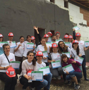 group of volunteer ADP associates in white T-shirts and red hardhats