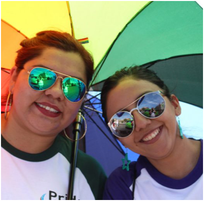 two female ADP associates sharing a rainbow-colored umbrella