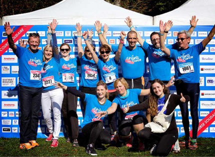 group of ADP associates in blue T-shirts waving their hands in the air; participating in 'enfants sans cancer' event