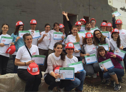 group of ADP associates wearing white T-shirts and red hardhats