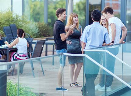 Skupina zaměstnanců ADP při diskuzi na terase.