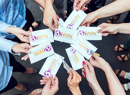 a circle of hands holding iWIN cards