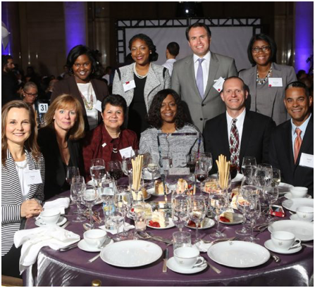 group of ADP associates seated and standing around a formal dinner table