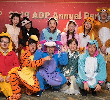 Men and women dressed in hooded animal onesie pajamas posing for a picture in front of a sign that reads 2019 ADP Annual Party