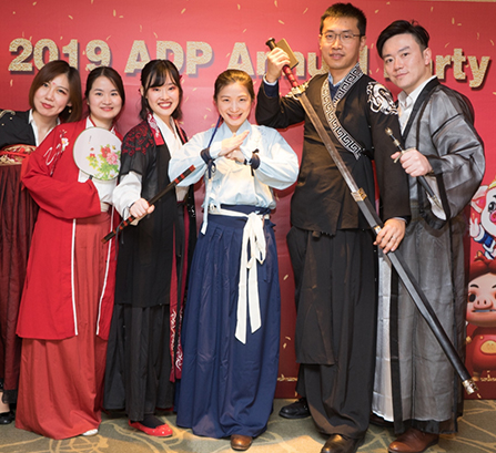 Men and women dressed in traditional Chinese fashion posing for a photo in front of a sign that reads 2019 ADP Annual Party