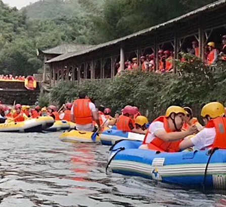 A large group of people rafting down the river wearing orange life vests and yellow and red helmets