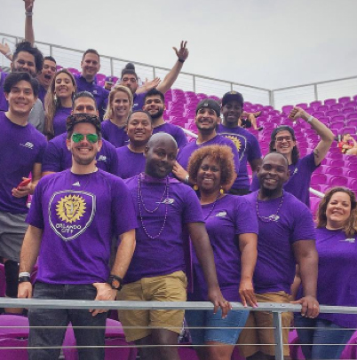 large group of ADP associates in purple t-shirts standing in stadium stands