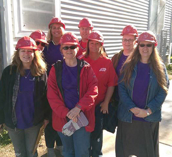 group of ADP associates wearing purple T-shirts and red construction hardhats