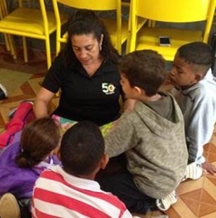 žena, která čte příběh skupince menších dětí