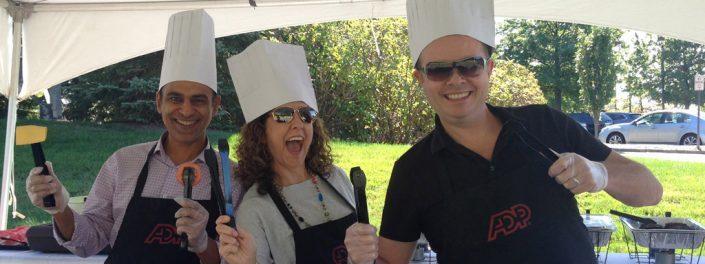 tři zaměstnanci ADP v kuchařských čepicích a s nástroji na grilování